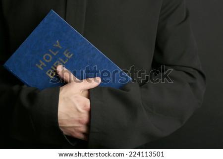 Man holding Bible on dark background - stock photo