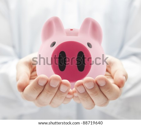 Man holding big pink piggy bank - stock photo