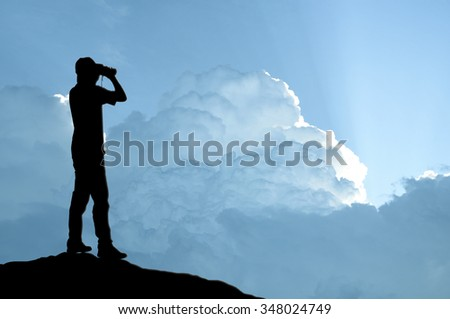 Man holding binocular on sunlight background