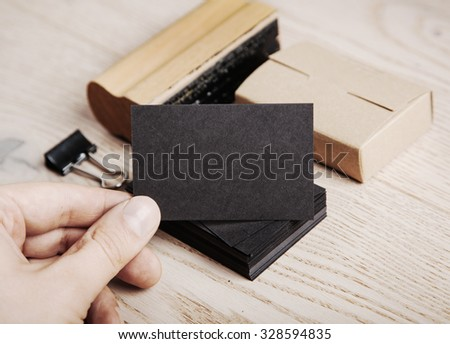Man holding black business card. Set of blank office elements on the wooden background.