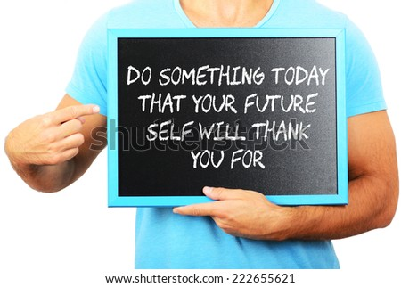 Man holding blackboard in hands and pointing the word DO SOMETHING TODAY THAT YOUR FUTURE SELF WILL THANK YOU FOR - stock photo