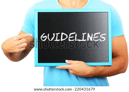 Man holding blackboard in hands and pointing the word GUIDELINES - stock photo