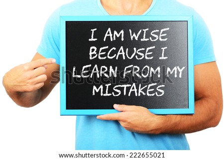 Man holding blackboard in hands and pointing the word I AM WISE BECAUSE I LEARN FROM MY MISTAKES - stock photo