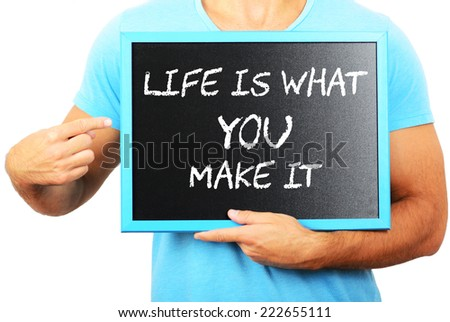 Man holding blackboard in hands and pointing the word LIFE IS WHAT YOU MAKE IT - stock photo
