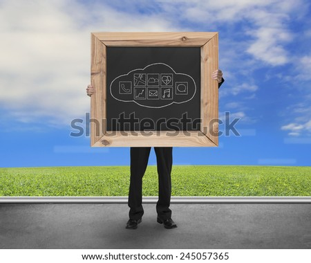 Man holding blackboard with hand-drawn cloud app icons on concrete floor and natural sky grass background - stock photo