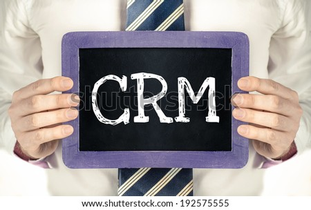 Man holding blackboard with word CRM - stock photo
