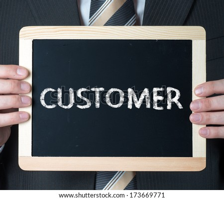 Man holding blackboard with word Customer - stock photo