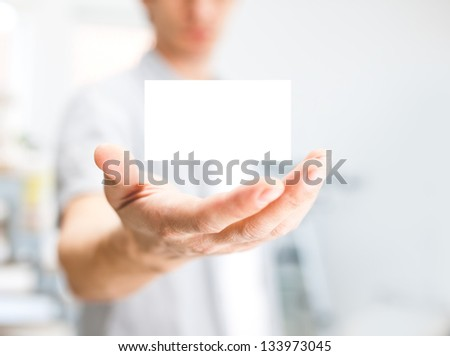 Man holding blank business card with copy space, small dof - stock photo