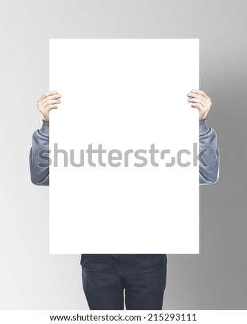 man holding blank paper on gray background - stock photo