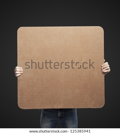 man holding blank poster on a black background - stock photo