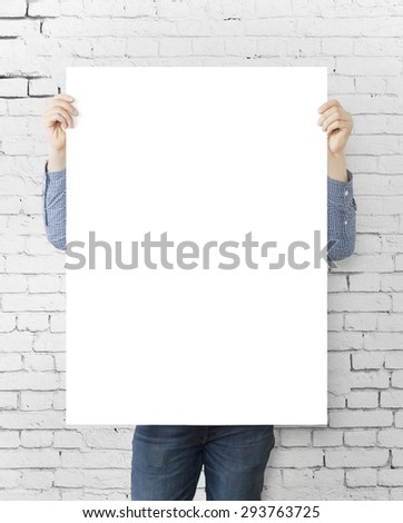man holding blank poster on brick wall background - stock photo