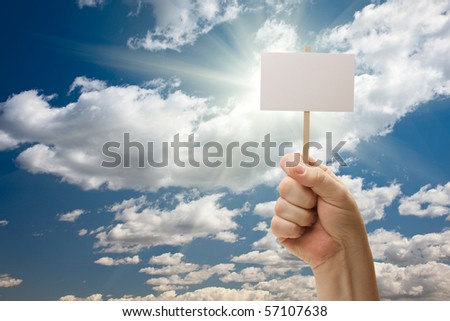 Man Holding Blank Sign Over Dramatic Clouds and Blue Sky with Sun Rays - Ready For Your Own Message on Sign and Over Clouds. - stock photo