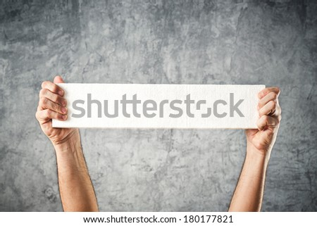 Man holding blank white banner with copy space for your text. - stock photo