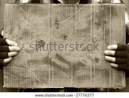 man holding blank worn out cardboard sign - stock photo