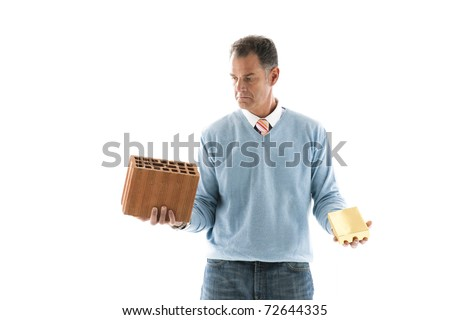 Man Holding brick and a gold bar; Concepts: investing on houses or financial investment - stock photo