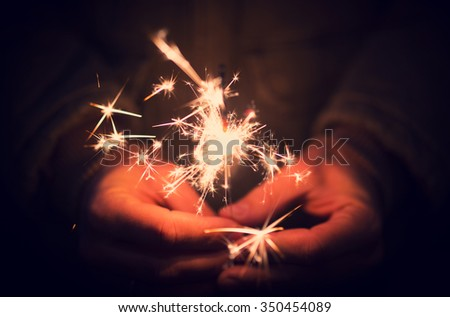 Man holding bright festive Christmas sparkler in hand, tinted photo - stock photo