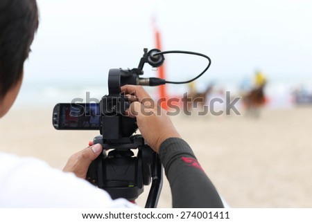 Man holding camcorder as working recording on a beach Polo Tournament sport - stock photo
