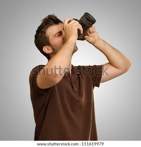 Man Holding Camera On Gray Background