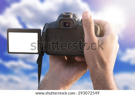 Man holding camera with blank screen and take a photo - stock photo