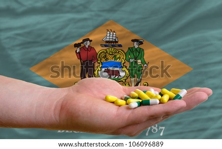 man holding capsules in front of complete wavy american state flag of delaware symbolizing health, medicine, cure, vitamines and healthy life - stock photo