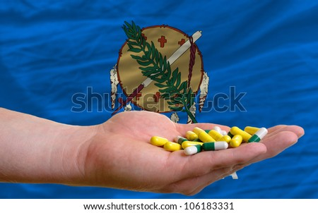 man holding capsules in front of complete wavy american state flag of oklahoma symbolizing health, medicine, cure, vitamins and healthy life - stock photo