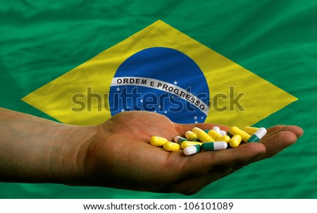 man holding capsules in front of complete wavy national flag of brazil symbolizing health, medicine, cure, vitamins and healthy life
