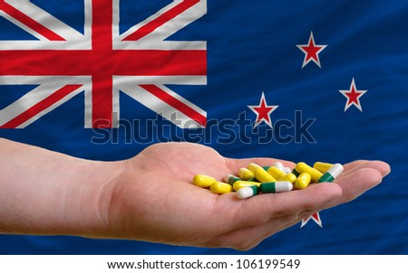 man holding capsules in front of complete wavy national flag of new zealand symbolizing health, medicine, cure, vitamins and healthy life