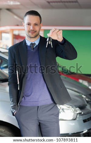 Man holding car keys in a garage - stock photo