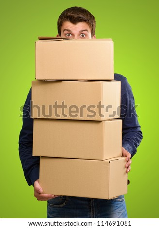 Man holding cardboard boxes on green background - stock photo