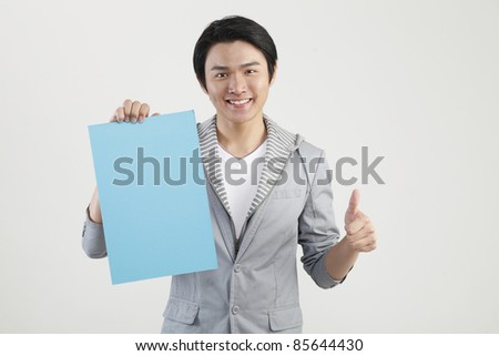 man holding cardboard with thumbs up - stock photo