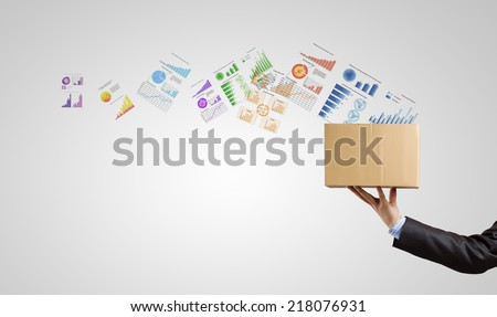 Man holding carton box with graphs and diagrams flying out - stock photo