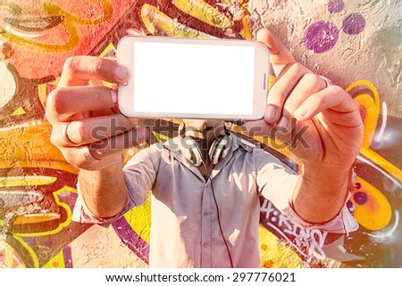 Man holding cell phone with blank screen and doing selfie  - stock photo