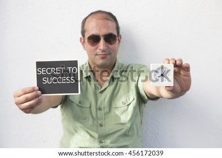 man holding chalkboard and clock with SECRET TO SUCCESS message,