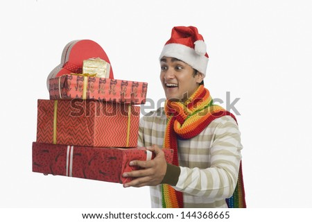 Man holding Christmas presents and smiling - stock photo