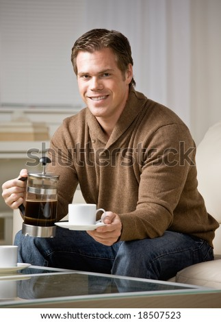 Man holding coffee carafe pouring cup of fresh coffee - stock photo