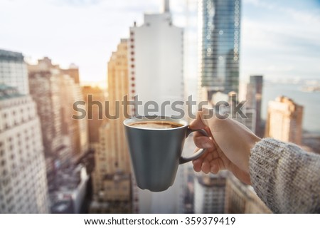 Man holding coffee cup in luxury penthouse apartments with view to New York City Manhattan downtown at the morning - stock photo