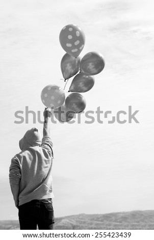 Man holding colorful balloons outside - stock photo