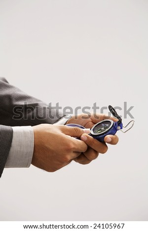 man holding compass looking at the direction - stock photo
