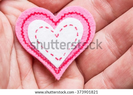 Man holding cotton heart in his hand.