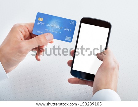 Man Holding Credit Card And Cell Phone Checking Account Balance - stock photo