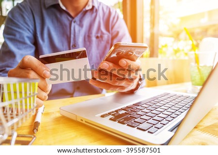 Man holding credit card in hand and entering security code using laptop keyboard. - stock photo