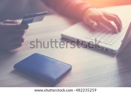 Man holding credit card. Laptop and wallet on the table. Online shopping (Intentional sun glare and lens flares)