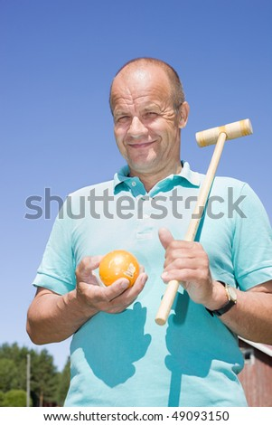 Man holding croquet club on his shoulder - stock photo
