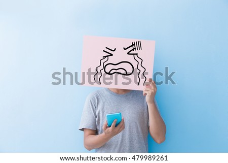 man holding cry expression billboard and take phone isolated on blue background