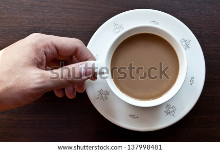 man holding cup of coffee on background