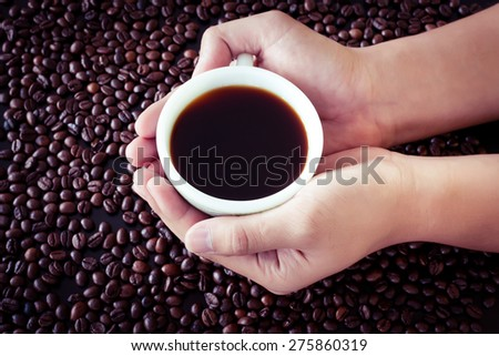 Man holding cup of freshly brewed coffee - stock photo