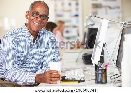 Man Holding Cup Working At Desk In Busy Creative Office - stock photo