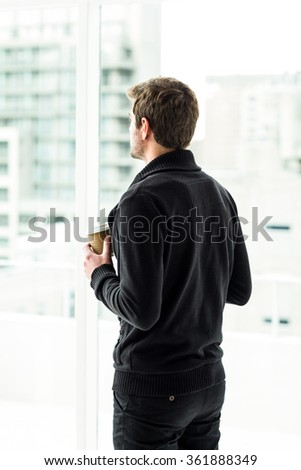 Man holding disposable cup looking out window in office - stock photo
