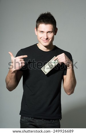 Man holding dollar on gray background - stock photo
