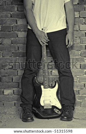 man holding electric guitar, grunge colors - stock photo